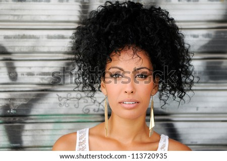 Portrait of a young black woman, model of fashion in urban background, with afro hairstyle - stock photo