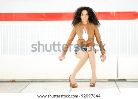 Portrait of a young black woman model of fashion, wearing camel colored jacket and shorts - stock photo