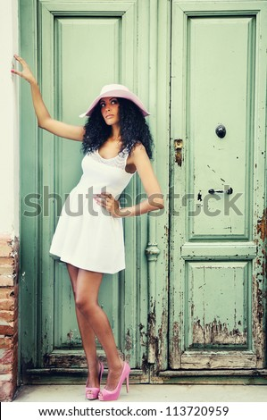 Portrait of a young black woman, model of fashion wearing dress and sun hat, with afro hairstyle - stock photo