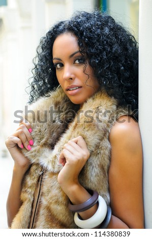 Portrait of a young black woman, model of fashion, wearing fur vest with afro hairstyle in urban background