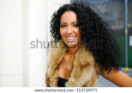 Portrait of a young black woman, model of fashion, wearing fur vest, with braces and afro hairstyle in urban background - stock photo