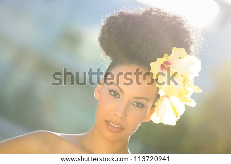 Portrait of a young black woman, model of fashion, with big flowers in her hair