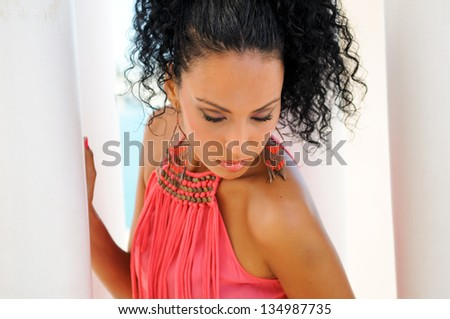 Portrait of a young black woman, model of fashion, with pink dress and earrings. Afro hairstyle - stock photo
