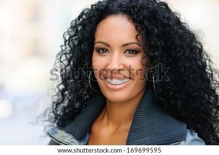 Portrait of a young black woman smiling with braces  - stock photo