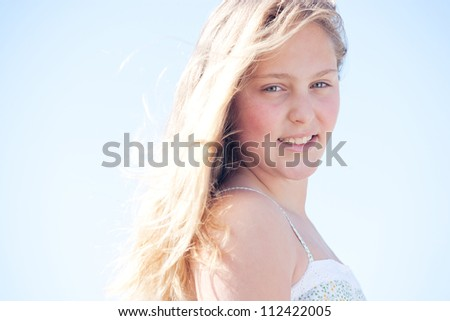 Portrait of a young blond girl with her hair floating in the breeze, turning and smiling against a blue sky. - stock photo