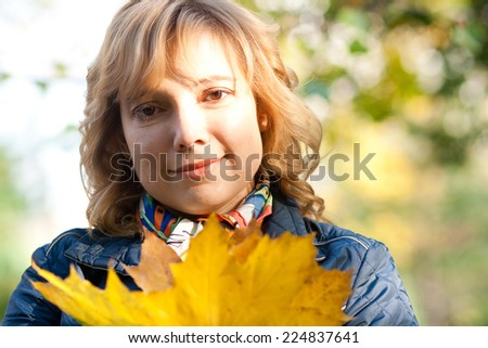 Portrait of a young blond woman holding maple leaves