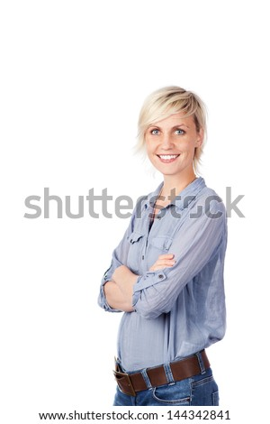 Portrait of a young blond woman in blue shirt standing with arms crossed against white background - stock photo