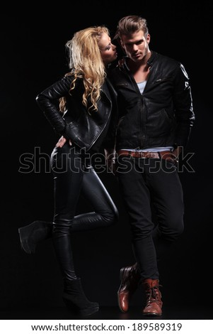 portrait of a young blonde woman telling something to her boyfriend while holding a hand on her hip and a leg raised . on black background - stock photo