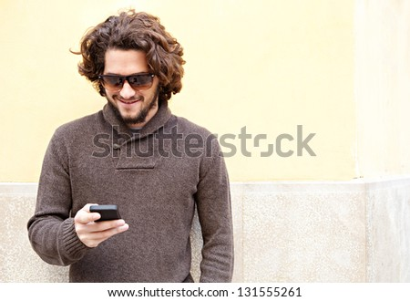"""Portrait of a young bohemian man using his """"smart phone"""" while leaning on a yellow wall, smiling outdoors. - stock photo"""