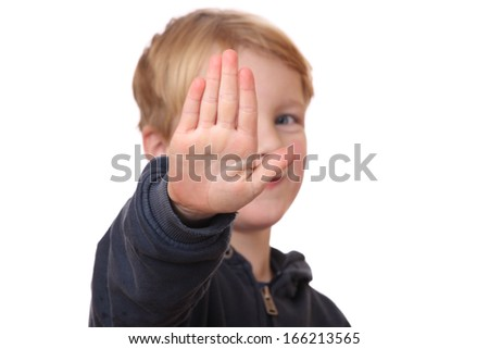 Portrait of a young boy holding out hand, indicating stop - stock photo