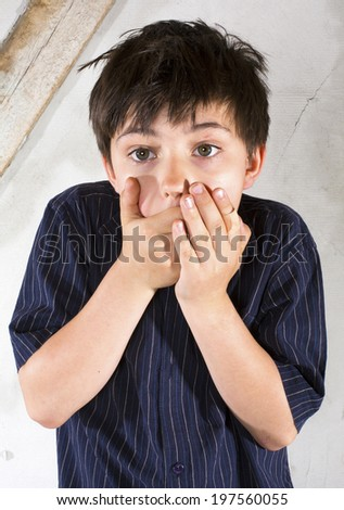 portrait of a young boy in a shirt with his hands on his mouth looking scraed and surprised - stock photo