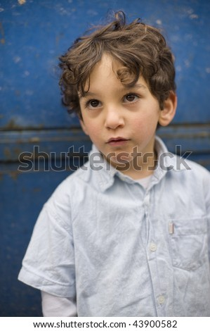 portrait of a young boy in front of a grungy blue background