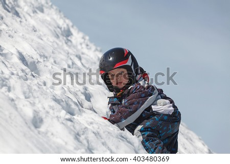 Portrait of a young boy in the snow (shallow DOF) - stock photo