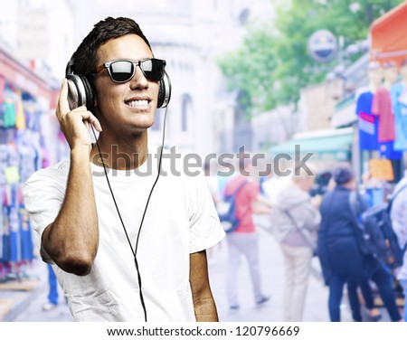 portrait of a young boy listening to music against a street background - stock photo