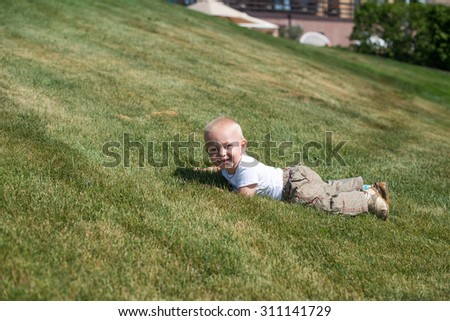 Portrait of a young boy lying in the grass - stock photo
