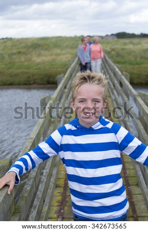 Portrait of a young boy on a bridge with his family in the background. He is smiling at the camera and wearing casual clothing.  - stock photo