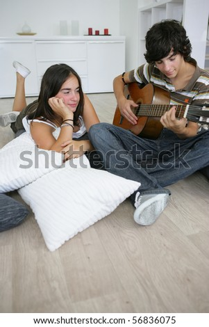 Portrait of a young boy playing guitar near a young girl - stock photo