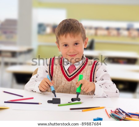 Portrait of a young boy sitting at his desk at school - stock photo
