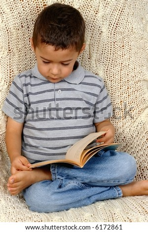 Portrait of a young boy sitting on a crocheted afghan blanket reading a book