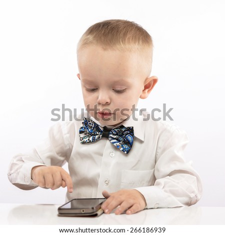 portrait of a young boy sitting with a mobile phone at the table in a white shirt. On a white background - stock photo