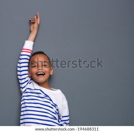 Portrait of a young boy smiling with arm raised and pointing finger up against gray background - stock photo