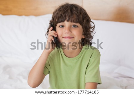 Portrait of a young boy using mobile phone in bed at home - stock photo