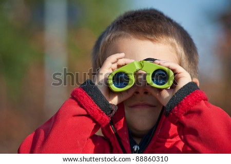 Portrait of a young boy with binoculars. Front view. - stock photo
