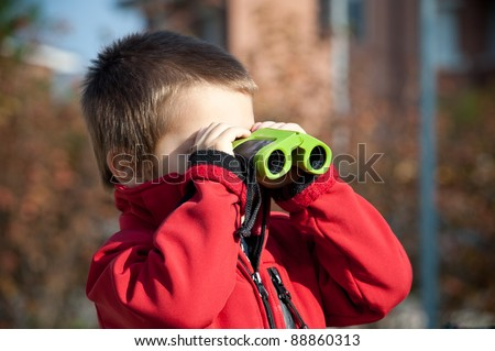 Portrait of a young boy with binoculars. Lateral view. - stock photo
