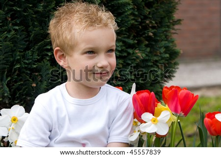 Portrait of a young boy with flowers. - stock photo