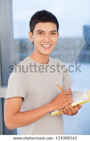 Portrait of a young boy with textbook - stock photo