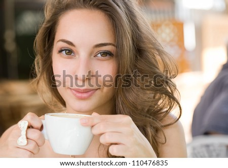 Portrait of a young brunette beauty enjoying her coffee. - stock photo