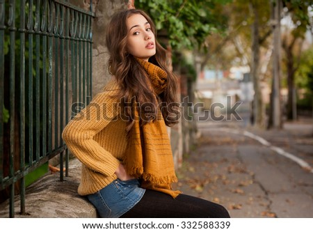Portrait of a young brunette beauty in autumn clothes.