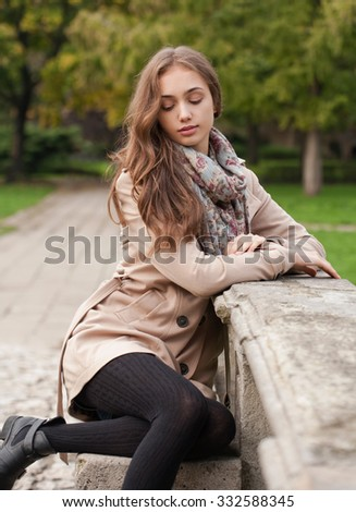 Portrait of a young brunette beauty in autumn clothes. - stock photo