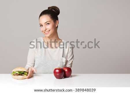 Portrait of a young brunette beauty offering nutrition choices. - stock photo