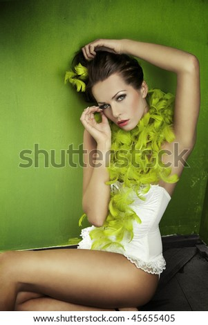 Portrait of a young brunette beauty over green wall - stock photo