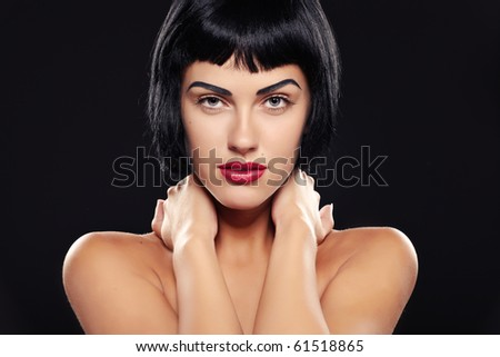 Portrait of a young brunette lady on black background - stock photo
