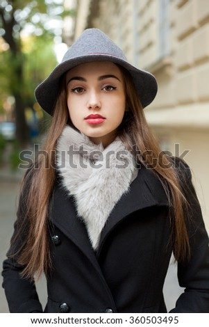 Portrait of a young brunette woman wearing elegant winter fashion.