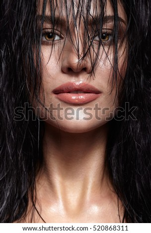 Portrait of a young brunette woman with hining wet make-up and shiny moist long hair hairdo