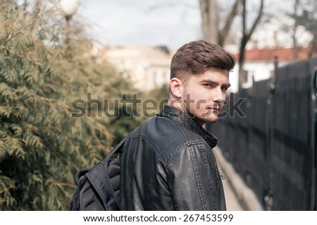 Portrait of a young brutal man with hipster hairstyles wearing leather jacket. Close-up, toned photo - stock photo