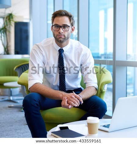 Portrait of a young business entrepreneur sitting in a modern open office space, looking at the camera with his laptop and a takeaway coffee - stock photo