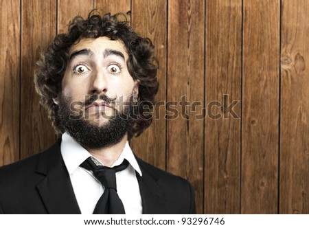 portrait of a young business man doing a dali imitation against a wooden wall - stock photo