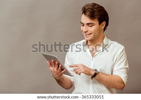 Portrait of a young business man in white shirt, use a Tablet PC on a gray background - stock photo