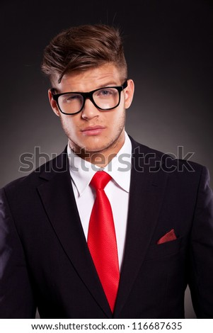 portrait of a young business man looking at the camera with raised eyebrow, on dark background - stock photo