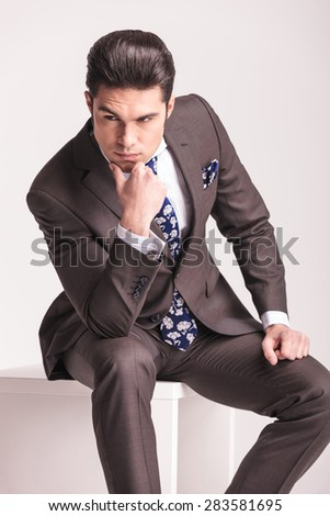 Portrait of a young business man sitting on a white chair while holding his hand to the chin, thinking. - stock photo
