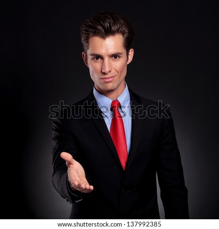 portrait of a young business man standing against a black background putting his hand out for a handshake while smiling to the camera - stock photo