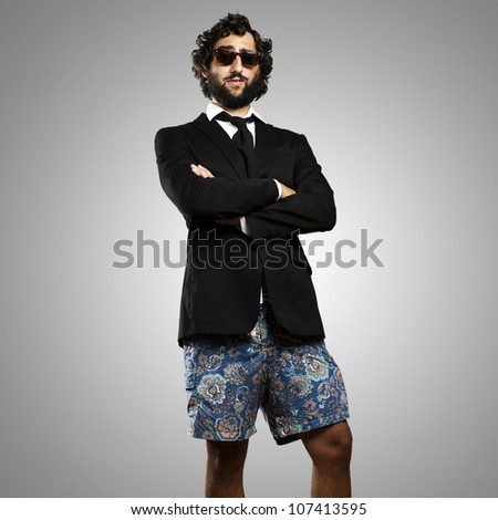 portrait of a young business man wearing a swimsuit against a grey background