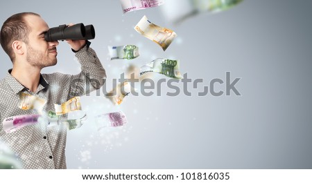 Portrait of a young business man with binoculars looking to the future. Money rain surrounding him - stock photo