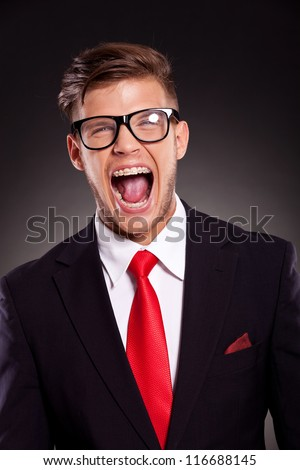 portrait of a young business man with eyeglasses shouting with mouth wide open, on dark background - stock photo