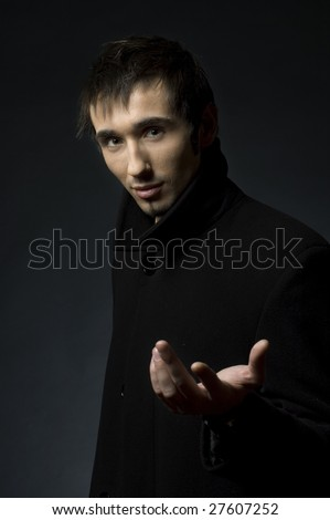 Portrait of a young business man with his hands on a dark background - stock photo