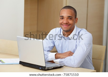 Portrait of a young business man working on a laptop - stock photo